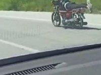 Üzerine uzandığı motosikletle tehlikeli yolculuk