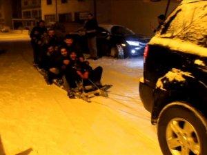 Arabanın arkasına bağladıkları merdivenle karda kaydılar